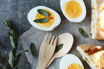 Boiled egg, wooden fork and spoon decorated with green leafs and bread. Top view