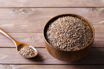 flax seeds in wooden bowl on rustic background