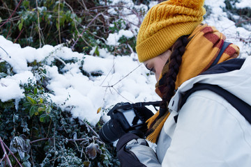 Portrait of beautiful woman with digital camera on winter snow day wearing winter yellow and white clothes.