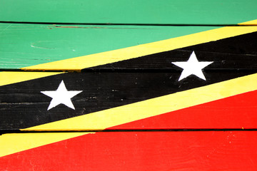 Flag of St Kitts & Nevis painted on wooden planks, in bright colours of red, yellow, green & black.