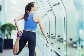 Portrait of young Caucasian woman doing exercises on open terrace of modern fitness club. Fitness concept