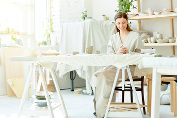 Cheerful woman in grey kimono sitting by table in her workroom and making creative items from ceramic clay