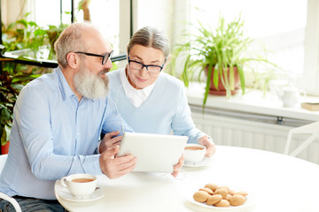 Contemporary senior couple with tablet and earphones talking through video-chat while sitting in cafe by cup of tea with cookies