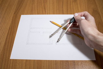 Person drawing a house project with compass and pencil on a table