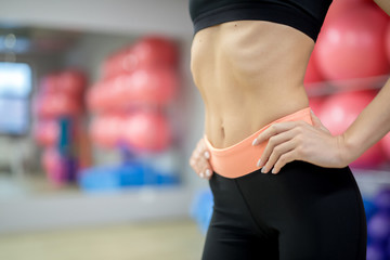 Mid-section of fit and slim girl in activewear keeping her hands on waist during workout in gym