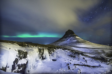 Colorful Aurora Borealis or better known as The Northern Lights and winter milky way over Kirkjufell, Iceland with starry night milkyway.