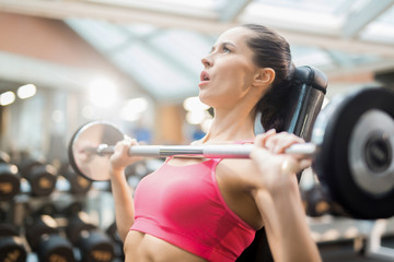 Young woman trying to lift heavy barbell from her chest while working out in gym