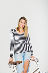 Young blonde woman in casual outfit with white bike smiling. Studio lighting, no retouch.