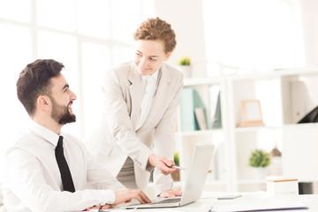 Businesswoman explaining to her partner presentation on computer