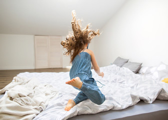 little girl jumping at home on bed