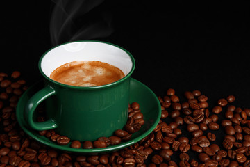 strong black coffee in a mug of emerald color on a black matte background