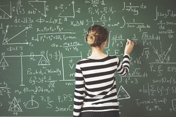 Young student writing with chalk on green chalk board in classroom