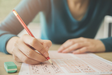 Female student holding pencil and examination paper