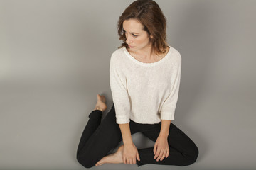casual fashion model sitting on gray background