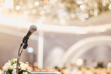 Microphone on the speech podium over the Abstract of conference hall or seminar room with attendee and bokeh, Business meeting concept.