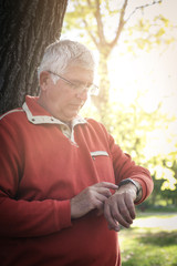 Senior man in sports clothing leaning on tree and checking time on watch.