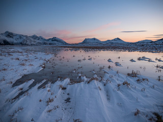 pretty sunset over frozen lake and snow covered coast, mountains in the distance and reflection on ice, room for text