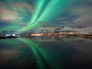 perfect northern lights reflection in the arctic water on lofoten islands