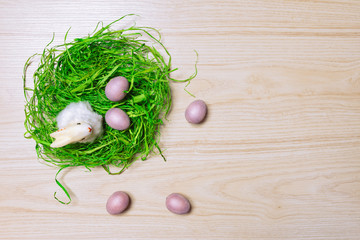 Easter decorations on wooden background with grass, rabbit and eggs. Top view.