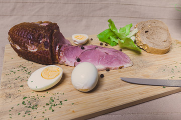 Smoked ham, eggs and bread on wooden board with spices.