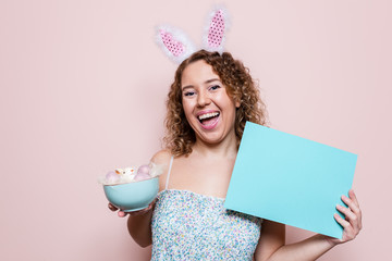 Beautiful woman hold easter decorations and blank poster with bunny ears on pink color background with copy space.
