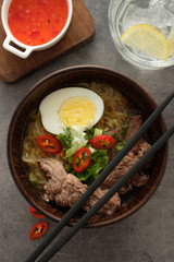Asian ramen soup with beef, egg, chives in bowl on grey background.