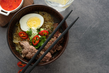 Asian ramen soup with beef, egg, chives in bowl on grey background. Copyspace. Top view