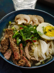 Closeup of Asian ramen soup with beef, egg, chives in bowl.