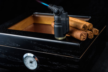 Cigars on a humidor against a black background