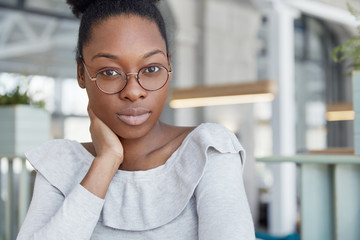 People, ethnicity and facial expressions concept. Confident businesswoman in glasses, wears casual clothing, listens seriously partner, suggest her own strategy of developing, models indoor.