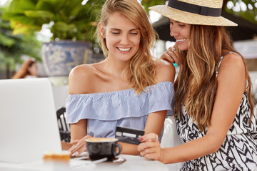 Photo of pleased two females in summer clothing, make purchase online with credit card on laptop computer, choose something in internet webstore, drink coffee in restaurant. Joyful women enjoy lesiure