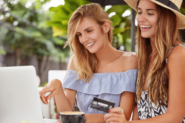 Outdoor shot of attractive female holds credit card, sits near her friend, look together into laptop computer, choose purchase to buy, make shopping online, connected to wireless high speed internet.
