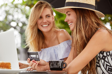 Pleased brunette young female in staw hat happy to recieve salary, spend money on online shopping, spends leisure time with friend in cafe, enjoy coffee. People, ecommerce and payment concept