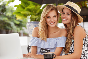 Portrait of delighted friendly young women with attractive looks, sit close to each other in cafe, surrounded with laptop copmputer, use plastic card for paying online, enjoy hot aromatic coffee