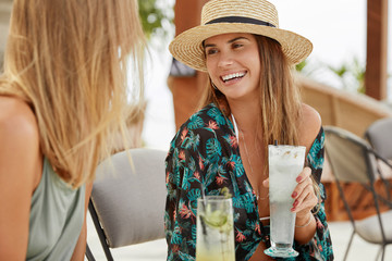 Happy women have pleasant talk while meet at summer party, drink alcoholic cocktails, rejoice having vacation or day off, look with glad expression at each other. People and leisure time concept