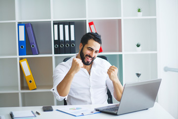 Excited young businessman celebrate victory cheerful in modern office