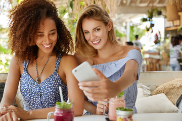 Shot of beautiful women have summer holidays, sit together against cafe interior, pose for selfie, photograph themselves, use modern mobile phone, drink fruit smoothie. People, rest, lifestyle