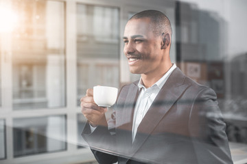 Waist up portrait of handsome businessman looking into the distance with happy smile while savour cup of tea. Man is on the other side window of cabinet
