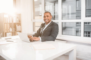 Waist up portrait of young handsome businessman sitting at office while gaining text on laptop. Guy looking with very happily smile at camera