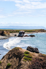 Pacific ocean, rocky beach and a cliff panorama landscape, in Estero Bluffs State Park