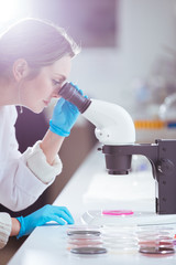 woman scientist looking through a microscope in laboratory