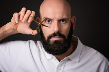 close up portrait of bearded man with scissors,isolated  over dark background