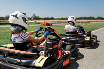 Girl with a guy riding a karting. outdoor activities in summer
