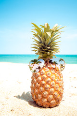 Hipster pineapple with sunglasses on a sandy beach. concept of fashion in summer. vintage color tone filter effect
