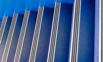 Foto op Plexiglas Trappen escalier avec moquette bleue et nez de marches en aluminium
