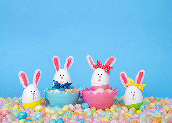 Craft Easter Bunnies made from plastic eggs Two in baskets full of candy with two standing in pastel jelly beans with a light blue background. Fun Easter line up with copy space