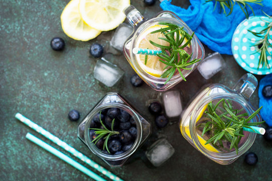 Mason jar mugs with homemade refreshing drink with blueberries and rosemary. The concept of proper nutrition and health or detoxification. Copy space, top view of a flat background.