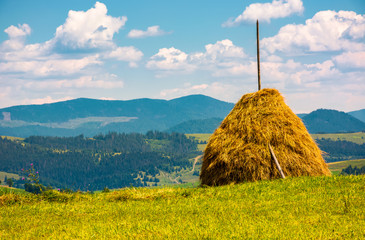 haystack on a grassy field on top of a hill