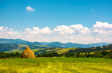haystack on a grassy field on top of a hill. beautiful mountainous countryside scenery in summer