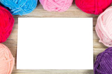 Semicircle of pastel colored yarn on the wooden table blank white landscape paper in the center